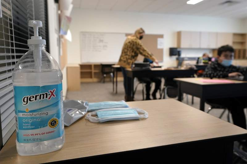 Hand sanitizer, wipes, and surgical masks rest on a desk in a fourth-grade classroom, Tuesday, Feb. 2, 2021, at Elk Ridge Elementary School in Buckley, Wash. (AP Photo/Ted S. Warren)