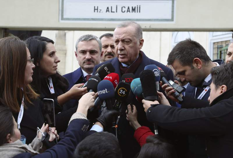 """Turkey's President Recep Tayyip Erdogan speaks to the media after Friday prayers, in Istanbul, Friday, Jan. 17, 2020.  Erdogan expressed doubt that Khalifa Hifter, the head of the self-styled Libyan National Army, would abide by the cease-fire. """"This man is not a trust-worthy man,"""" he told reporters in Istanbul, """" yesterday, they continued to bomb Tripoli."""" (Presidential Press Service via AP, Pool)"""