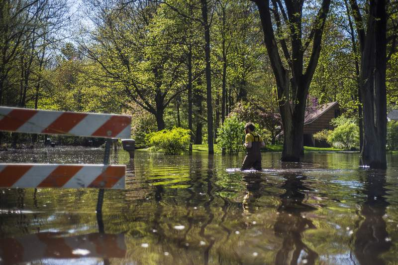 Nick Fox wades through floodwater to reach his home on Nurmi Drive, Wednesday, May 20, 2020, in Midland, Mich. (Katy Kildee/Midland Daily News via AP)
