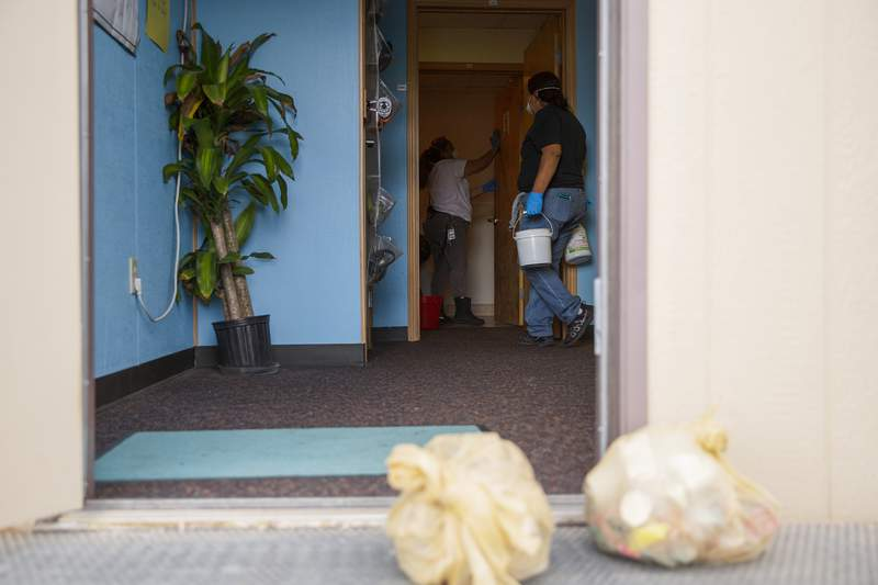 In this Wednesday, Nov. 20, 2019 photo, custodians at Grand Mesa Middle School work on disinfecting a classroom in Grand Junction, Colo. Due to a contageous virus transmitted among students and staff members, district administrators have closed all 46 schools for cleaning until after next weeks Thanksgiving break. (McKenzie Lange/Grand Junction Sentinel via AP)