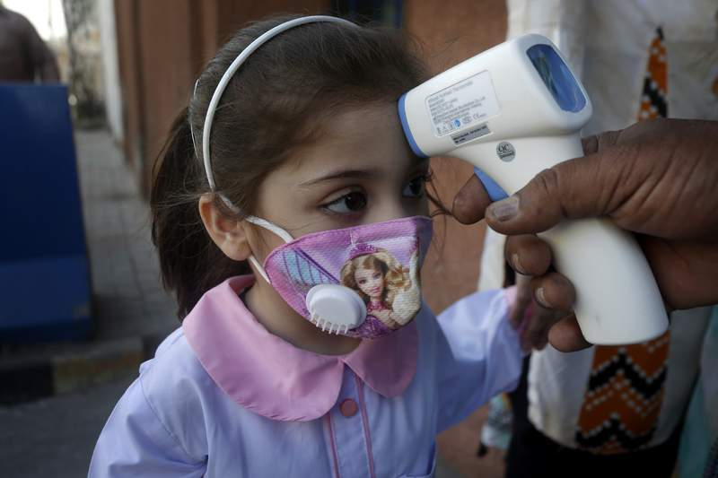 A worker checks the body temperature of a student on her arrival at a primary school in Lahore, Pakistan, Wednesday, Sept. 30, 2020. (AP Photo/K.M. Chaudary)