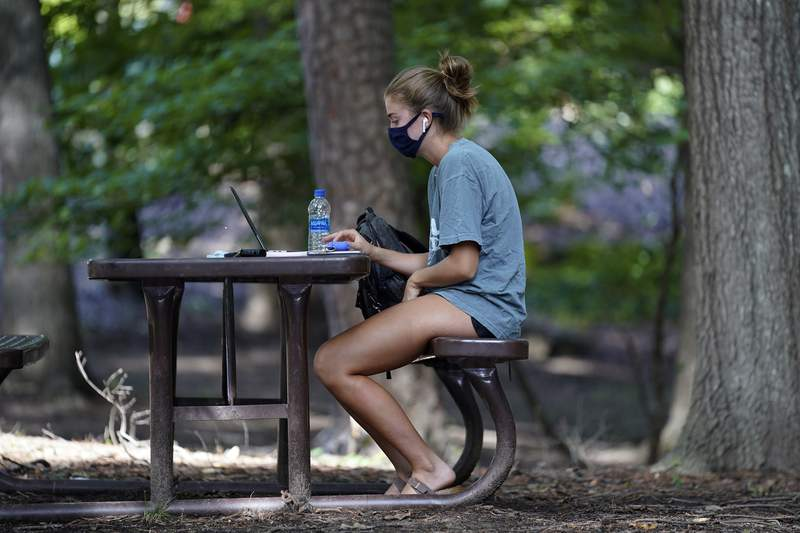 FILE - In this Aug. 18, 2020, file photo, a student works outside Ehrighaus dormitory on campus at the University of North Carolina in Chapel Hill, N.C. As more and more schools and businesses around the country get the OK to reopen, some college towns are moving in the opposite direction because of too much partying and too many COVID-19 infections among students. (AP Photo/Gerry Broome, File)