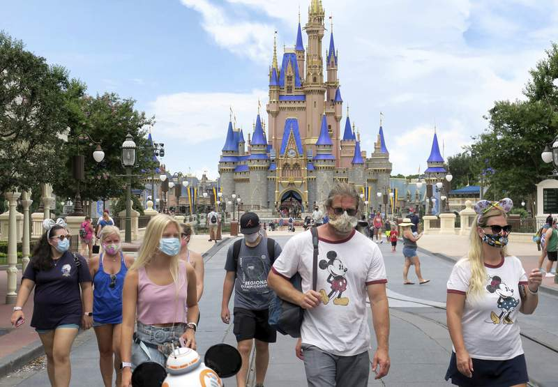 Guests wear masks as required to attend the official reopening day of the Magic Kingdom at Walt Disney World in Lake Buena Vista, Fla., Saturday, July 11, 2020. Disney reopened two Florida parks, the Magic Kingdom and Animal Kingdom, Saturday, with limited capacity and safety protocols in place in response to the coronavirus pandemic. (Joe Burbank/Orlando Sentinel via AP)