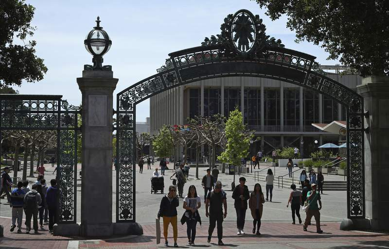 """FILE - In this May 10, 2018, file photo, students walk past Sather Gate on the University of California at Berkeley campus in Berkeley, Calif. A California state audit found that the University of California wrongly admitted at least 64 wealthy students over the past six years as """"favors to donors, family, and friends."""" California State Auditor Elaine Howle also found in the audit released Tuesday, Sept. 22, 2020, that campus staff falsely designated 22 of the applicants as student-athlete recruits because of donations from or as favors to well-connected families. The University of California, Berkeley, admitted 42 less-qualified applicants based on connections to staff, leadership, and donors. (AP Photo/Ben Margot, File)"""