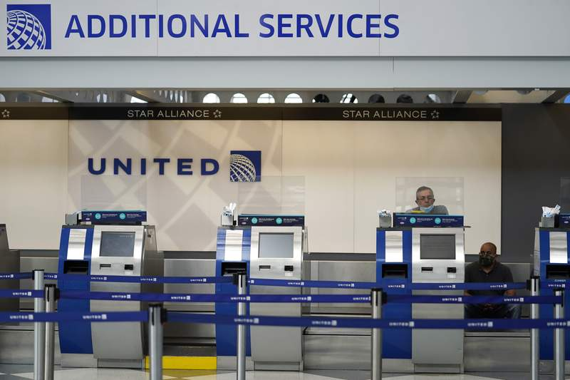 FILE - In this Oct. 14, 2020 file photo, United Airlines employees work at ticket counters in Terminal 1 at O'Hare International Airport in Chicago.  United Airlines will pay more than $49 million to settle criminal and civil accusations of defrauding the post office in the handling of international mail. The Justice Department said Friday, Oct. 26, 2021, that former employees of Uniteds cargo division falsified parcel delivery information for several years.  (AP Photo/Nam Y. Huh, File)