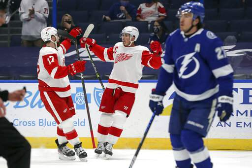 Detroit Red Wings' Dylan Larkin, center, celebrates his goal with Filip Hronek, of Czech Republic, as Tampa Bay Lightning's Ryan McDonagh reacts during the first period of an NHL hockey game Sunday, April 4, 2021, in Tampa, Fla. (AP Photo/Mike Carlson)