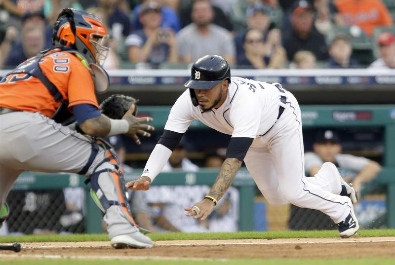 Detroit Tigers' Harold Castro dives into home plate to score against Houston Astros' Martin Maldonado on a single by Jonathan Schoop during the fifth inning of the second baseball game of a doubleheader Saturday, June 26, 2021, in Detroit. (AP Photo/Duane Burleson)
