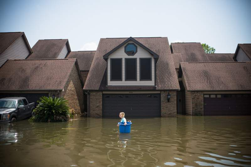 Jenna Fountain carries a bucket down Regency Drive to try to recover items from their flooded home in Port Arthur, Texas, on Sept. 1, 2017.