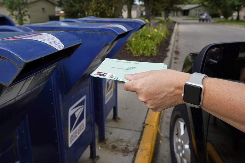 A person drops into a mail box applications for mail-in ballots, in Omaha, Neb., Tuesday, Aug. 18, 2020. (AP Photo/Nati Harnik)