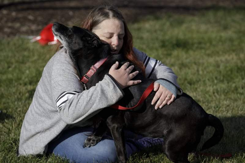 Debra Mejeur hugs her dog Lola Saturday, Dec. 5, 2020, outside DuPage County Animal Services, in Wheaton, Ill., as they reunite three years after Lola went missing during a trip to suburban Chicago. (Youngrae Kim/Chicago Tribune via AP)
