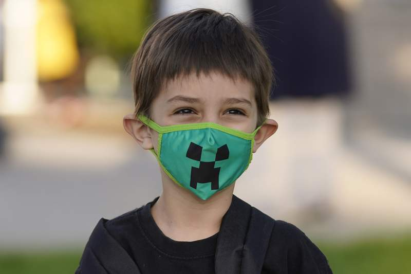 Adam Shallbetter, who is going into kindergarten, poses as his mother takes a photograph, after arriving at Whittier Elementary School Tuesday, Aug. 24, 2021, in Salt Lake City. Kids in Salt Lake City are headed back to school Tuesday wearing masks after the mayor issued a mandate order despite heavy restrictions on mask mandates imposed by the GOP-dominated Legislature. (AP Photo/Rick Bowmer)
