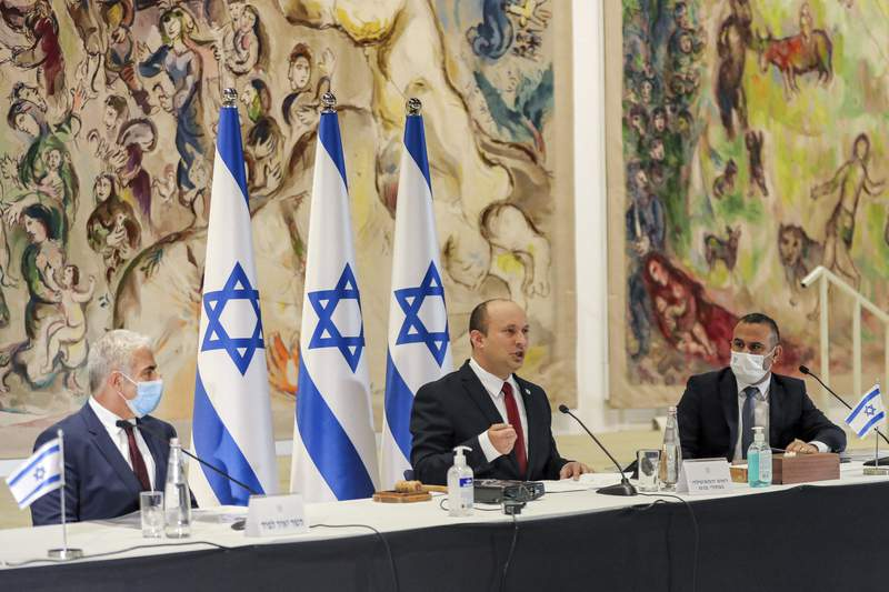 Israeli Prime Minister Naftali Bennett, center, chairs the weekly cabinet meeting as Alternate Prime Minister and Foreign Minister Yair Lapid, left, looks on, at the Knesset in Jerusalem Monday, July 19, 2021. (Gil Cohen-Magen/Pool Photo via AP)