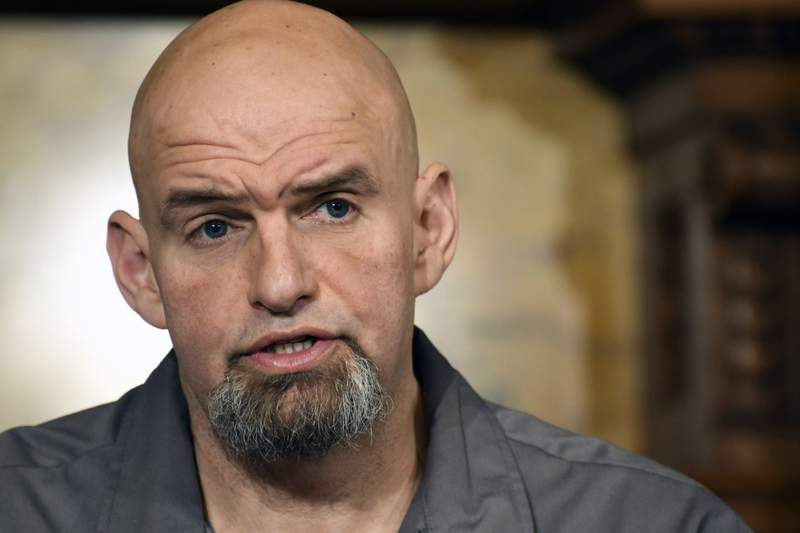 FILE - In this Thursday, Jan. 24, 2019  file photo, Pennsylvania Lt. Gov. John Fetterman speaks at a news conference in the governor's Capitol reception room in Harrisburg, Pa. A provision slipped into lame-duck budget legislation Friday, Nov. 20, 2020 would ban flags not approved by lawmakers from flying at the state Capitol  such as the pro-marijuana legalization and LGBTQ- and transgender-rights flags that Fetterman hangs from his second-floor outdoor balcony that overlooks the building's broad front steps. (AP Photo/Marc Levy, File)