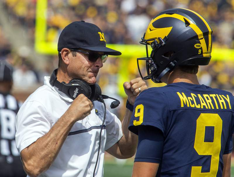Michigan head coach Jim Harbaugh gives encouragement to quarterback J.J. McCarthy (9) before the true freshman takes his first career snap in the third quarter of an NCAA college football game against Western Michigan in Ann Arbor, Mich., Saturday, Sept. 4, 2021.