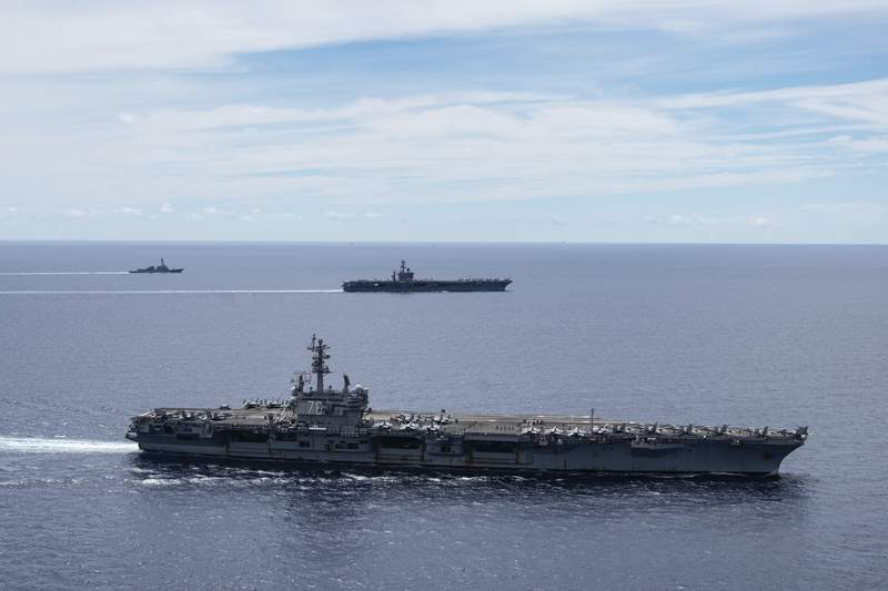 FILE - In this July 6, 2020, file photo provided by U.S. Navy, the USS Ronald Reagan (CVN 76, front) and USS Nimitz (CVN 68, rear) Carrier Strike Groups sail together in formation, in the South China Sea. The U.S. Navy says the aircraft carrier Ronald Reagan and its strike group entered the South China Sea earlier in August, 2020, and have been carrying out air operations.  China routinely objects to U.S. naval activity in the sea, especially when more than one strike group is present, as happened earlier this year, and when they involve operations with navies from other countries.  (Mass Communication Specialist 3rd Class Jason Tarleton/U.S. Navy via AP, File)