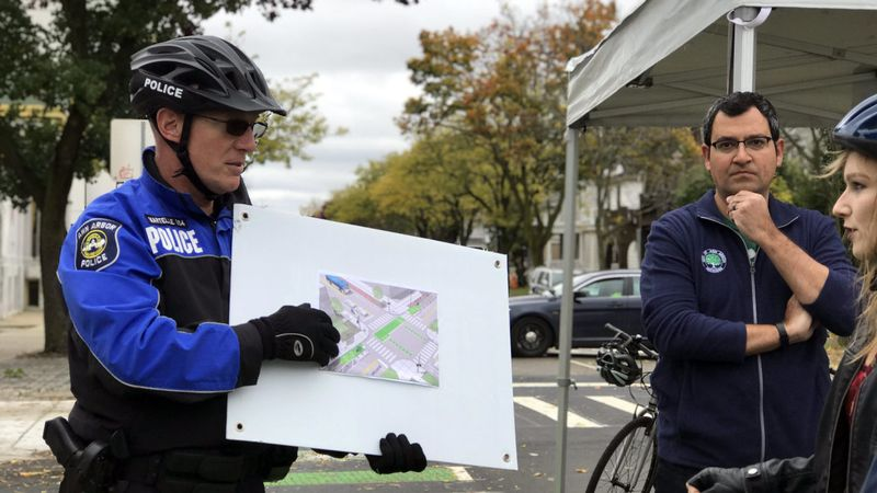 A police officer shows cyclists a map of the two-way protected bike lane on William Street. (Credit: Meredith Bruckner)