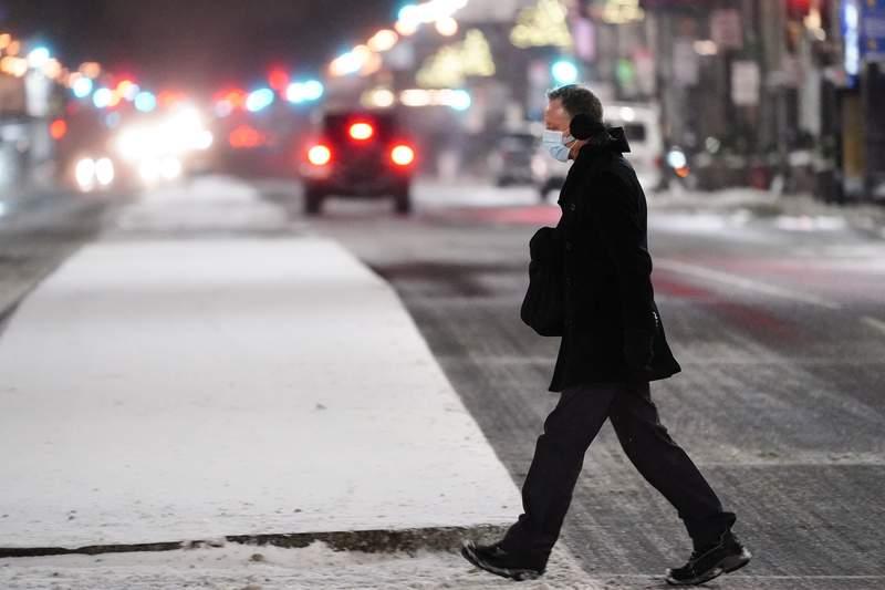 A person wearing a face mask as a precaution against the coronavirus walks during a winter storm in Philadelphia, Monday, Feb. 1, 2021. (AP Photo/Matt Rourke)
