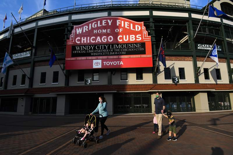 People wear face masks and walk outside of Wrigley Field before a baseball game between the Chicago Cubs and the Minnesota Twins, Sunday, Sept. 20, 2020, in Chicago. It will be the last home game of the season. (AP Photo/Matt Marton)