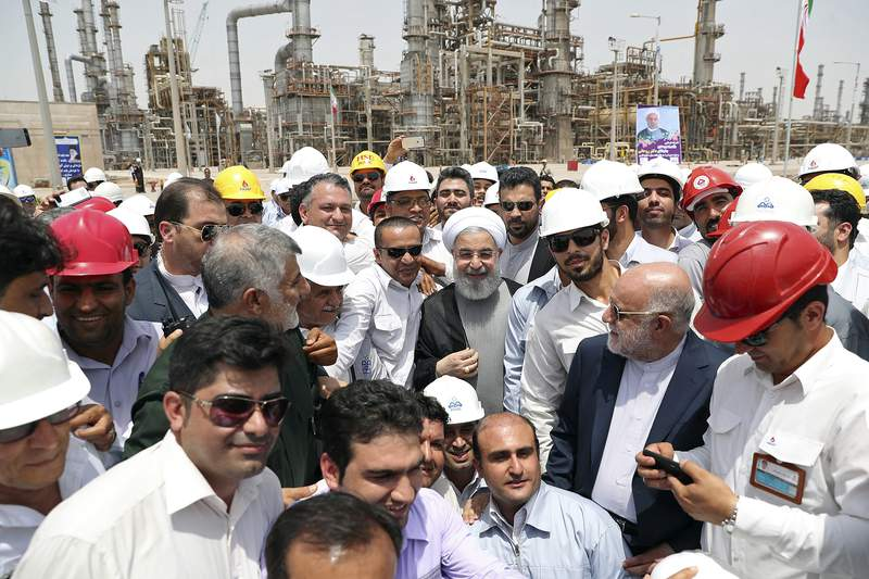 FILE - In this April 30, 2017 file photo, released by an official website of the office of the Iranian Presidency, Iranian President Hassan Rouhani, center, inaugurates the Persian Gulf Star Refinery in Bandar Abbas, Iran. Five Iranian tankers likely carrying at least $45.5 million worth of gasoline and similar products are now sailing to Venezuela as of Sunday, May 17, 2020, part of a wider deal between the two U.S.-sanctioned nations amid heightened tensions between Tehran and Washington. Analysts say the gasoline they carry came from the Persian Gulf Star Refinery. (Iranian Presidency Office via AP, File)