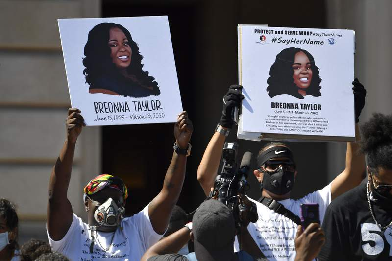 FILE - Signs are held up showing Breonna Taylor during a rally in her honor on the steps of the Kentucky State Capitol in Frankfort, Ky., Thursday, June 25, 2020. The city of Louisville will pay several million dollars to the mother of Breonna Taylor and install police reforms as part of a settlement of a lawsuit from Taylors family, The Associated Press has learned. (AP Photo/Timothy D. Easley, File)