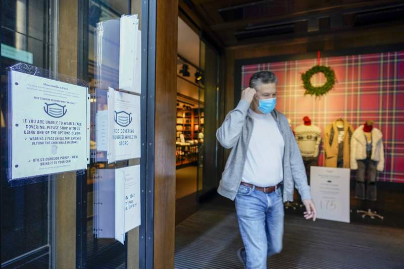 A Black Friday shopper adjusts his face mask as he leaves the Abercrombie & Fitch store along Fifth Avenue, Friday, Nov. 27, 2020, in New York. (AP Photo/Mary Altaffer)