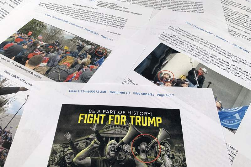 """This complaint supporting the arrest warrant for Owen Shroyer is photographed in Frederick, Md., Friday, Aug. 20, 2021. Court documents show that a host of the right-wing website Infowars, Owen Shroyer, has been charged in connection to the Jan. 6 riot at the U.S. Capitol. Shroyer, who hosts """"The War Room With Owen Shroyer"""" on the website operated by conspiracy theorist Alex Jones, faces misdemeanor charges such as disorderly conduct and entering a restricted area of Capitol grounds. (AP Photo/Jon Elswick)"""