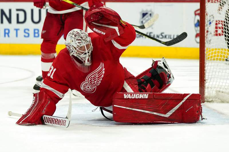 Detroit Red Wings goaltender Calvin Pickard deflects the puck during the third period of an NHL hockey game against the Columbus Blue Jackets, Saturday, March 27, 2021, in Detroit. (AP Photo/Carlos Osorio)