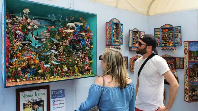 Attendees view art made by Nicario Jimenez at his booth at the Ann Arbor Street Art Fair, The Original. (Courtesy: Ann Arbor Art Fair)