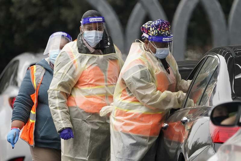 Workers administer a COVID-19 vaccine at a Los Angeles County site at the California State University Northridge, Tuesday, Feb. 9, 2021, in Northridge, Calif. (AP Photo/Marcio Jose Sanchez)