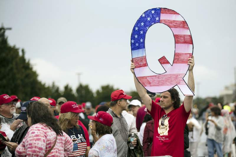 FILE - In this Aug. 2, 2018, file photo, a protesters holds a Q sign waits in line with others to enter a campaign rally with President Donald Trump in Wilkes-Barre, Pa. Candidates engaging with the QAnon conspiracy theory are running for seats in state legislatures this year, breathing more oxygen into a once-obscure conspiracy movement that has grown in prominence since adherents won Republican congressional primaries this year. (AP Photo/Matt Rourke, File)
