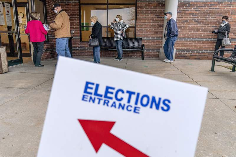 In this Oct. 29, 2020, photo, voters line up as the doors open to the Election Center for absentee early voting for the general election in Sterling Heights, Mich. (AP Photo/David Goldman)