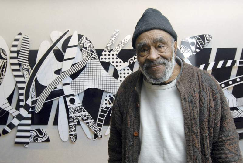 """Charles McGee in front of his piece titled """"Regeneration,"""" 2007. (Photo by Ray Manning)"""