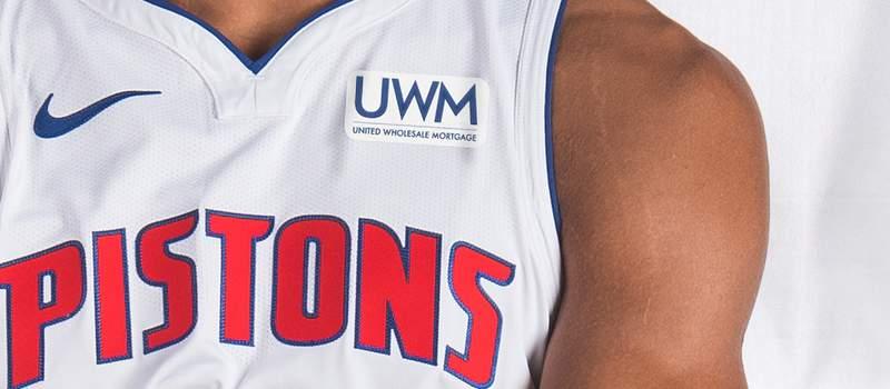 "United Wholesale Mortgage's ""UWM"" logo on Detroit Pistons jersey."