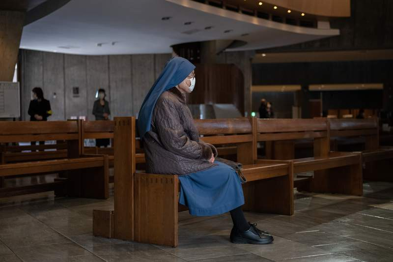 TOKYO, JAPAN - DECEMBER 25: A nun wears a face mask as she attends Christmas Day Mass at St. Mary's Cathedral on December 25, 2020 in Tokyo, Japan. As Christians around the world celebrate Christmas, many have had to adapt as the coronavirus (COVID-19) pandemic forces churches to close or implement measures such as social distancing and reduced services. (Photo by Carl Court/Getty Images)