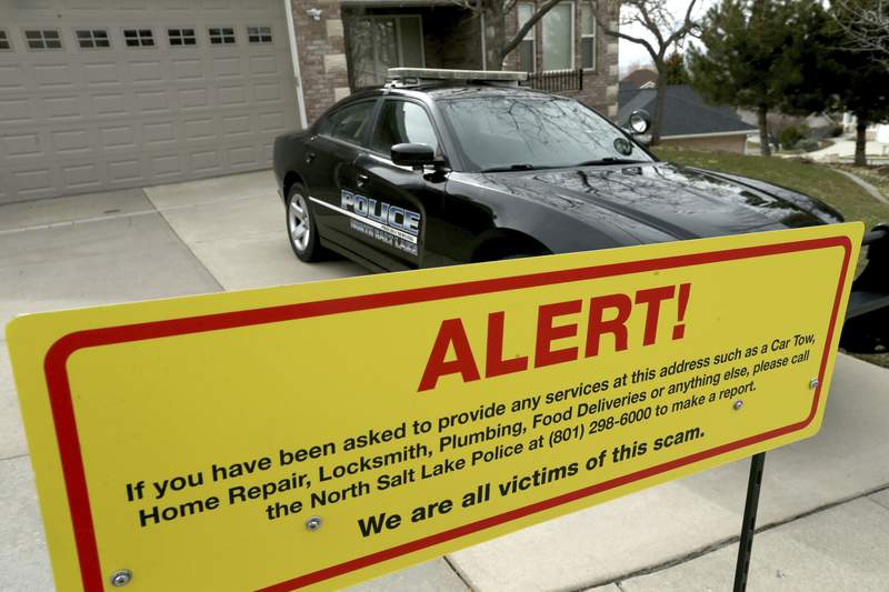 FILE - This March 21, 2019 file photo shows a warning sign and a police officer's vehicle at Walt Gilmore's home in North Salt Lake, Utah. U.S. prosecutors arrested Loren Okamura, a Hawaii man, on Nov. 22, who they accuse of sending hundreds of unwanted service providers to the Utah home, including plumbers and prostitutes. It's unknown why the Gilmores were targeted or what if any relationship exists between Okamura and the family. Homeowner Walt Gilmore told The Associated Press in March he couldn't discuss why a protective order was sought against Okamura but that he was sure the extreme stalking was not random. (Laura Seitz/The Deseret News via AP, File)