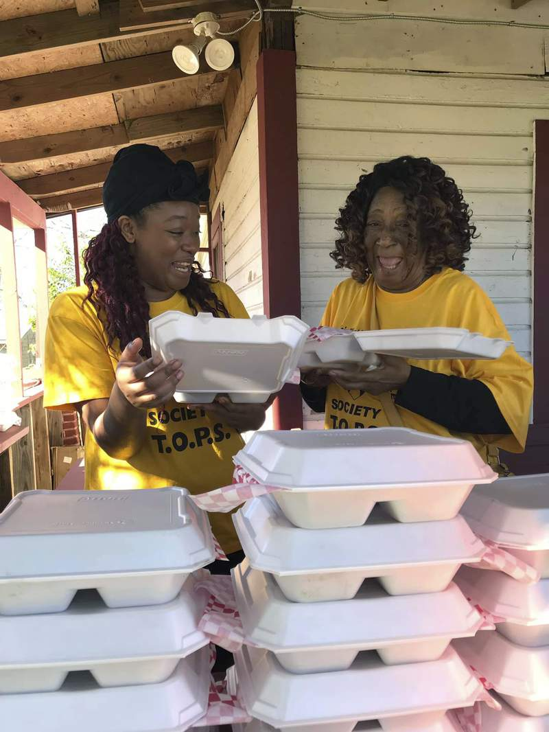 Tkeyah McGriff, left, and Tina Glasgow prepare lunches to be delivered to the homeless on Thanksgiving Day, Nov. 26, 2020, at TOPS/Momma Tina's Mission House in Dothan, Ala. The Ordinary People Society (TOPS) received a grant from the Southern Power Fund, which it is using to provide housing, food, personal hygiene products, and social services to people who have been released from prison. (Courtesy of The Ordinary People Society via AP)
