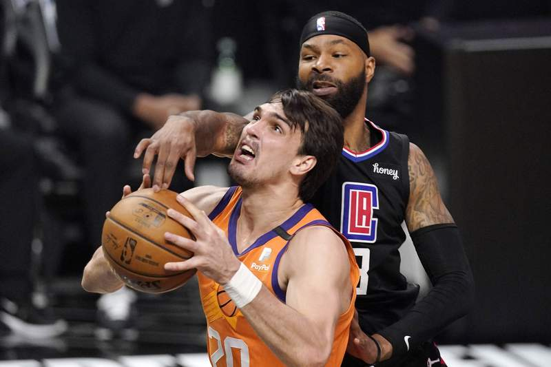 Phoenix Suns forward Dario Saric, left, shoots as Los Angeles Clippers forward Marcus Morris Sr. defends during the first half in Game 6 of the NBA basketball Western Conference Finals Wednesday, June 30, 2021, in Los Angeles. (AP Photo/Mark J. Terrill)
