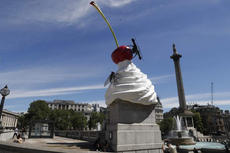FILE - In this Thursday, July 30, 2020 file photo, a woman takes a photo on her phone of the new work of art entitled 'The End' by artist Heather Phillipson which was unveiled on the fourth plinth in Trafalgar Square in London. A sculpture symbolizing Britains complex colonial ties and an artwork featuring the faces of 850 transgender people are set to go on display in Trafalgar Square, one of Londons highest-profile venues for public art. City officials on Monday July 5, 2021, announced the next two works to occupy the fourth plinth in the central London square. (AP Photo/Alastair Grant, File)
