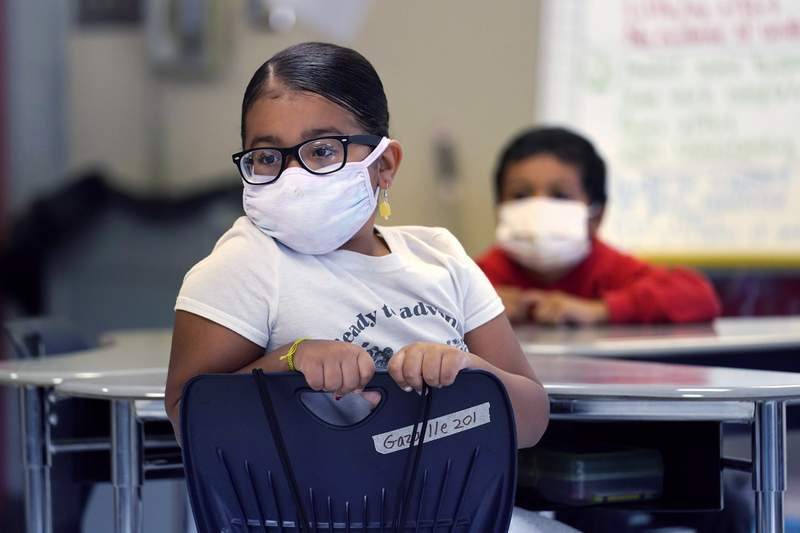 ADVANCE FOR USE THURSDAY, AUG. 26, 2021 AND THEREAFTER - A a summer school student wears a protective mask while listening to instruction, at the E.N. White School in Holyoke, Mass., on Wednesday, Aug. 4, 2021. Schools across the U.S. are about to start a new year amid a flood of federal money larger than they've ever seen before, an infusion of pandemic relief aid that is four times the amount the U.S. Department of Education sends to K-12 schools in a typical year. (AP Photo/Charles Krupa)