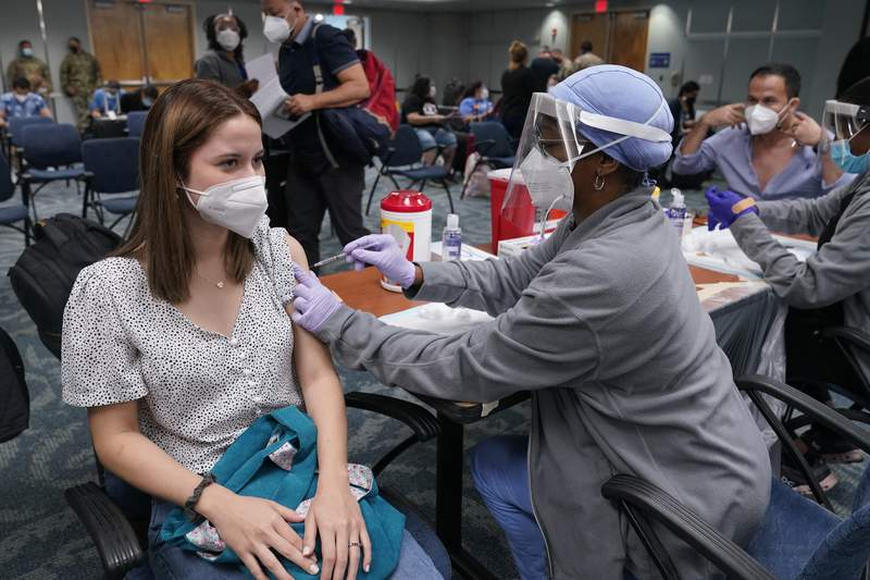 Natalia Dubom, of Honduras, gets the Johnson & Johnson COVID-19 vaccine at Miami International Airport, Friday, May 28, 2021, in Miami. The vaccine was offered to all passengers arriving at the airport. Florida's Emergency Management Agency is running the program through Sunday. (AP Photo/Marta Lavandier)
