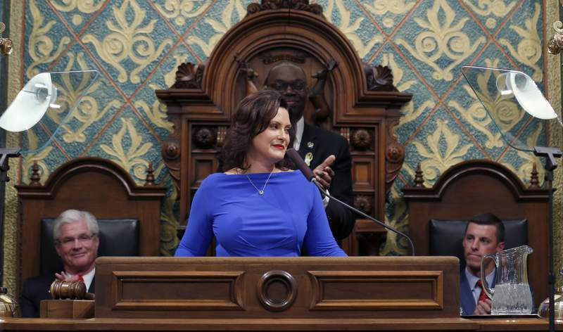 FILE - In this Feb. 12, 2019 file photo, Michigan Gov. Gretchen Whitmer delivers her State of the State address to a joint session of the House and Senate as Senate Majority Leader Mike Shirkey, House Speaker Lee Chatfield, right, and Lt. Gov. Garlin Gilchrist, rear, react, at the state Capitol in Lansing, Mich. A budget impasse in Michigan is starting to take a toll on government programs and services. Nearly two months ago, Democratic Gov. Whitmer vetoed an unprecedented $947 million in funding to restart broken-down budget talks. She and the Republican-led Legislature want to reverse some or many of her vetoes. But they remain at odds over Republicans push to curtail her powers after the first-year governor shifted funding within state departments. (AP Photo/Al Goldis File)