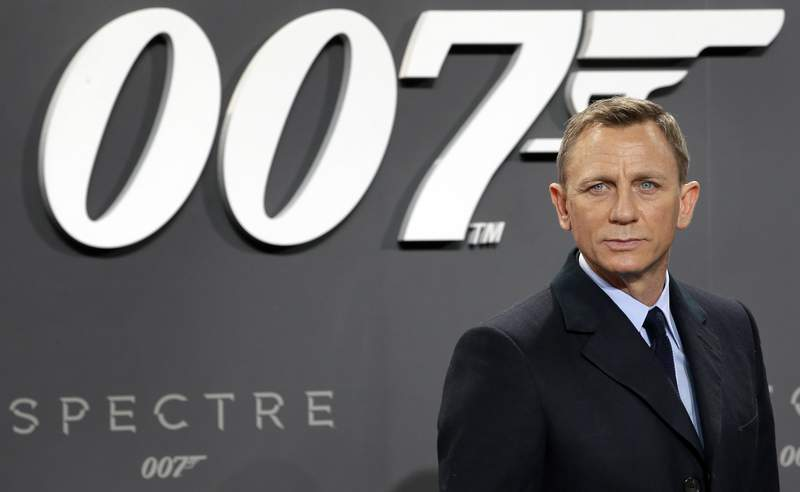 """FILE - This is a Wednesday, Oct. 28, 2015 file photo of actor Daniel Craig poses for the media as he arrives for the German premiere of the James Bond movie """"Spectre"""" in Berlin, Germany. The release of the James Bond film No Time to Die has been delayed again, this time to 2021, because of the effects of COVID-19 on the theatrical business. MGM, Universal and Bond producers, Michael G. Wilson and Barbara Broccoli, said on Twitter Friday that the 25th instalment in the franchise will now open globally on April 2, 2021. (AP Photo/Michael Sohn, File)"""