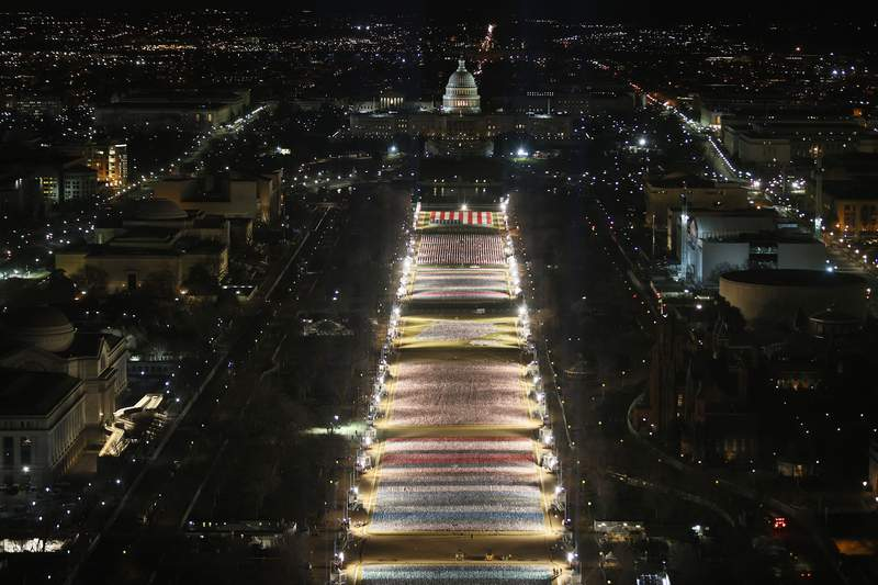"""The """"Field of Flags"""" is illuminated on the National Mall as the U.S Capitol Building is prepared for the inauguration ceremonies for President-elect Joe Biden on January 18, 2021 in Washington, DC. (Photo by Joe Raedle/Getty Images)"""