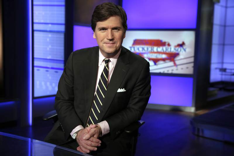 """FILE - In this Thursday, March 2, 2107 file photo, Tucker Carlson, host of """"Tucker Carlson Tonight,"""" poses for a photo in a Fox News Channel studio in New York. A video showing a Montana man confronting Carlson is circulating widely on social media after the man called the Fox News host """"the worst human being known to mankind."""" The video posted Friday, July 23, 2021, shows Dan Bailey talking to Carlson in close proximity inside a Montana fly fishing shop. (AP Photo/Richard Drew, File)"""