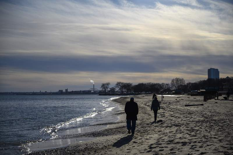 People enjoy a sunny winter day on the beach by Lake Michigan in Milwaukee, Wisconsin, on January 6, 2020. (Photo by Eric BARADAT / AFP)