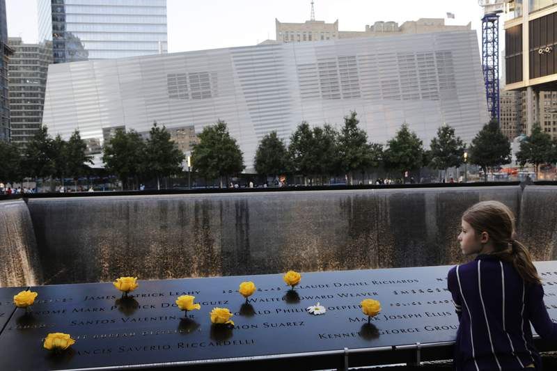 FILE - In this Sept. 8, 2013, file photo, Charlotte Newman, 8, visits the National September 11 Memorial and Museum in New York. On Sept. 11, 2020, Americans will commemorate 9/11 with tributes that have been altered by coronavirus precautions and woven into the presidential campaign. (AP Photo/Mark Lennihan, File)