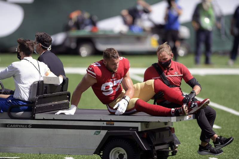 San Francisco 49ers defensive end Nick Bosa (97) is driven off the field after being injured during the first half of an NFL football game against the New York Jets Sunday, Sept. 20, 2020, in East Rutherford, N.J. After losing four players to knee injuries last week against the New York Jets, the Niners complained about a sticky new turf at MetLife Stadium and expressed some concern about returning to the same field a week later. (AP Photo/Bill Kostroun, File)