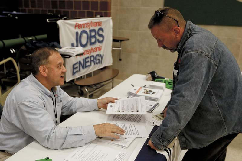 FILE - In this Nov. 2, 2017, photo, a recruiter in the shale gas industry, left, speaks with an attendee of a job fair in Cheswick, Pa. Hiring in the United States jumped in February 2020 as employers added a robust 273,000 jobs, evidence that the economy was in strong shape before the coronavirus began to sweep through the nation.(AP Photo/Keith Srakocic, File)