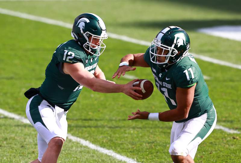 Rocky Lombardi #12 of the Michigan State Spartans hands the ball off to Connor Heyward #11 of the Michigan State Spartans in the second half of the game against the Rutgers Scarlet Knights at Spartan Stadium on October 24, 2020 in East Lansing, Michigan.