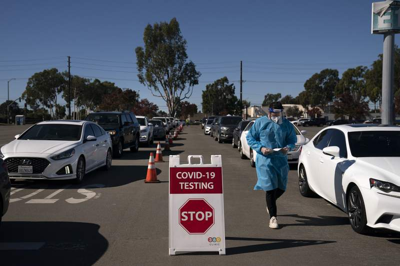 FILE - In this Nov. 16, 2020, file photo, student nurse Ryan Eachus collects forms as cars line up for COVID-19 testing at a testing site set at the Orange County Fairgrounds in Costa Mesa, Calif.